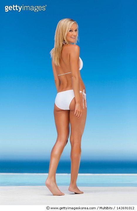 Woman wearing bikini by infinity pool - gettyimageskorea