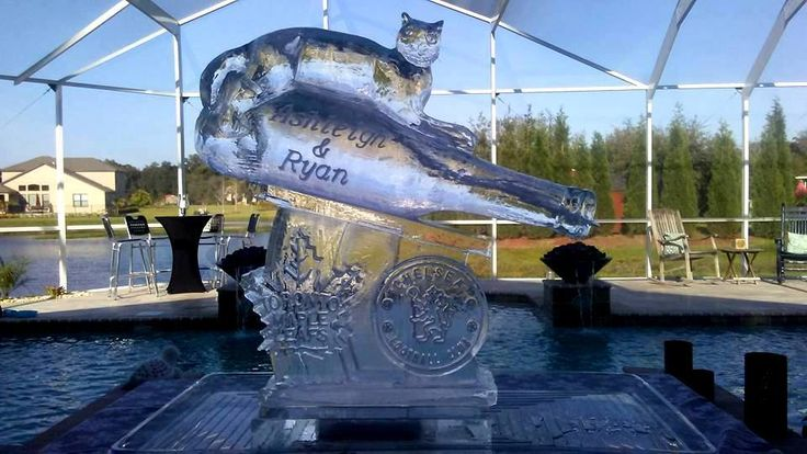 Ice luge of a bottle with a cat upon the bottle and the names of the bride and groom etched into the ice. #iceluges #icelugestampa