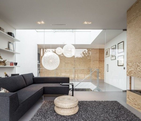 Gorgeous globe lights made of string illuminate the stairwell beyond the living room. The modern sofa adds texture to the space with rough wool upholstery as does the deep pile shag rug in shades of gray.