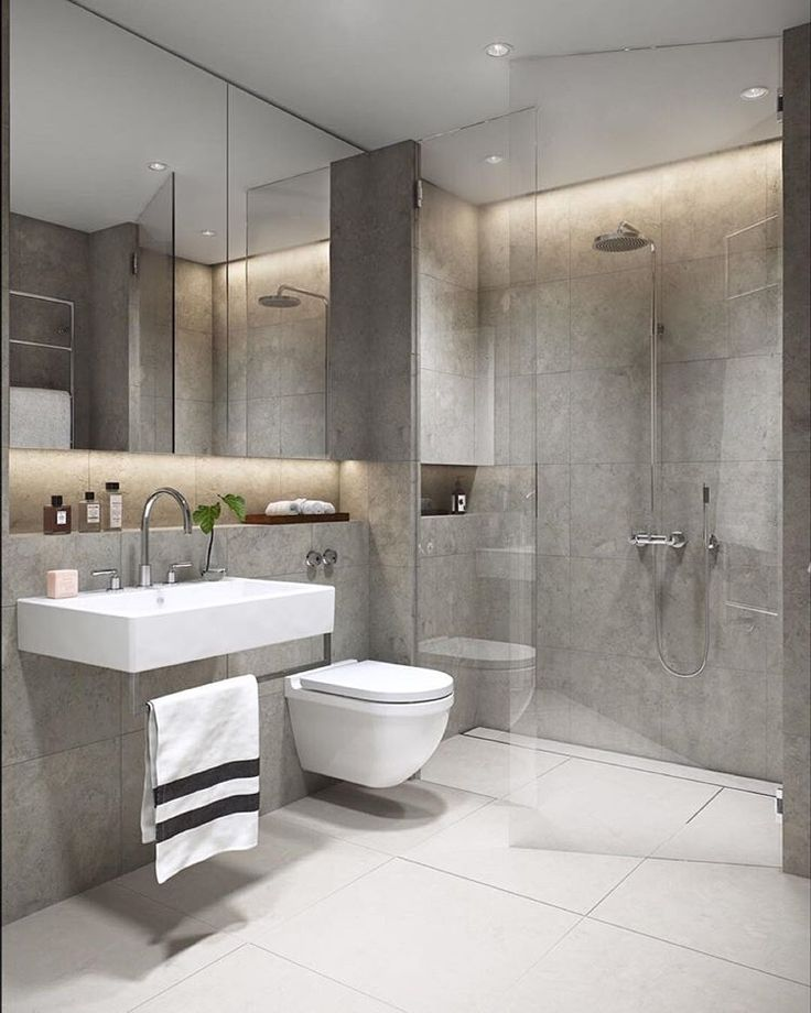 Simple and elegant bathroom with black tapware, large format grey tiles and free standing bath. Grey bathroom