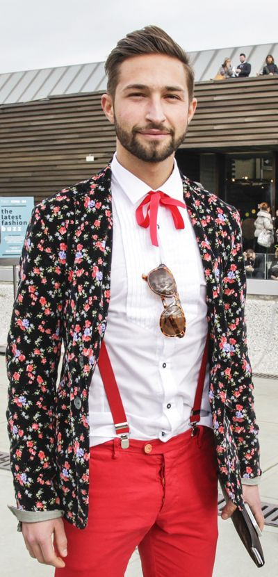 Hipster with red pants, floral blazer, white shirt and red bow-tie and sunglasses.