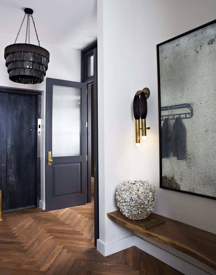 dramatic black entry with brass hardware and statement art//