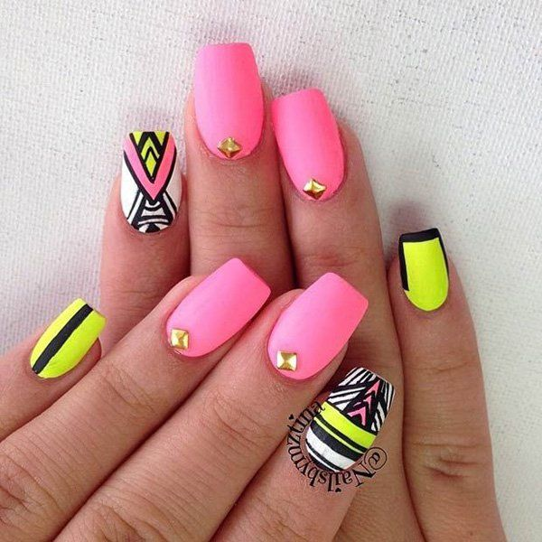 Tribal designs on a pink matte nail polish. Various other colors are used such as black, yellow and white to contrast the soft pink polish. Gold beads are added on top for accent.