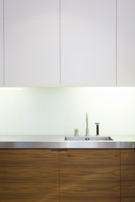 Minimalist.  White wall cabinets and wooden base cabinets with stainless steel counter top.