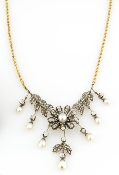 COLLIER en or gris et or jaune, stylisant une fleur dans un entourage feuillage retenant des pampilles ponctuees de perles fines. La chaine en or jaune. Poids brut : 28,6 g Avec son certificat du LFG… - Osenat - 16/12/2012
