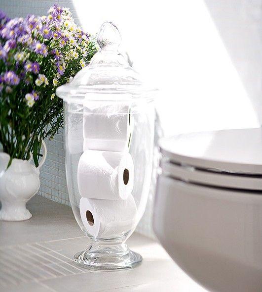 O decorativo pote de vidro com tampa guarda rolos sobressalentes de papel higiênico. Ninguém vai passar aperto