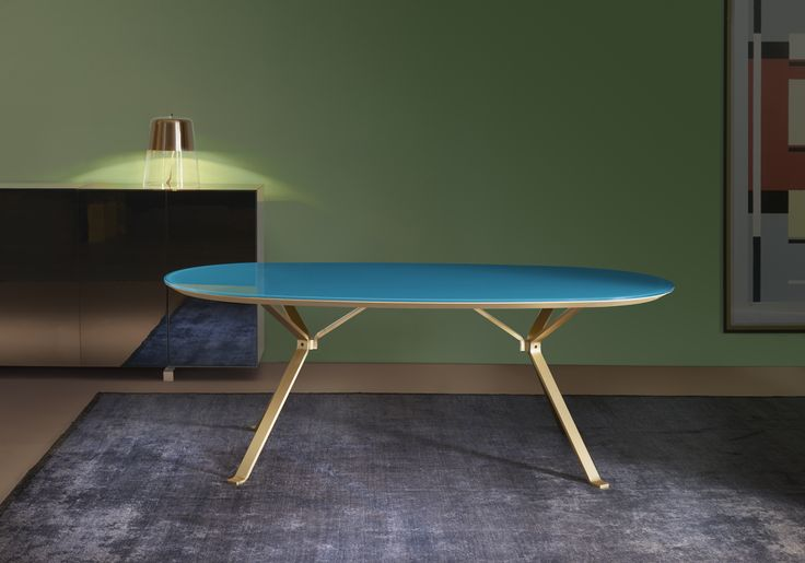 Revo table coll. Reflection with turquoise lacquered crystal oval glass top and satin gold steel legs. Product design by CMR, color design and finishes by Raffaella Mangiarotti #homeoffice #living # focusoncolor # humanoffice #glass #shining