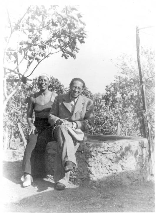 Lion Feuchtwanger Papers, 1884-1958 - Lion Feuchtwanger and wife Marta in their garden, Sanary, France, 1940-1950. Sitting among the trees they are both perched on a wall smiling for the camera.