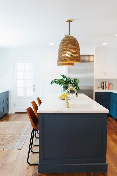 Lovely kitchen features white upper cabinets and navy lower cabinets painted Benjamin Moore Hale Navy paired with calacatta marble countertops.