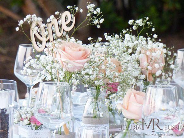 Centre de table, nom de table sous forme de numéro à l'anglaise, roses et gypsophile, petite bouteille de lait accessoirisée de toile de jute et de dentelle