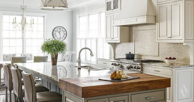 A gray kitchen island is topped with a white and grey granite countertop as well as an end piece ...