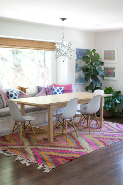 Add a bold chandelier and bright rug to your dining area. So inviting.