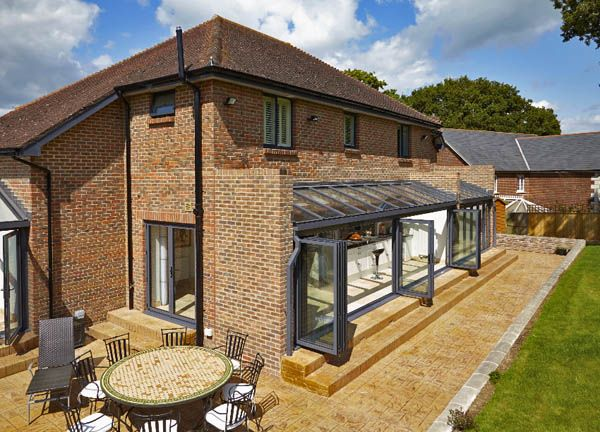 Beautiful long side return kitchen extension constructured on a 1970s detached home with glass folding doors