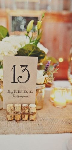 Table numbers, brown paper, corks and soft flowers.   To see my table number holders and for wedding inspiration: www.fb.com/labolaweddings