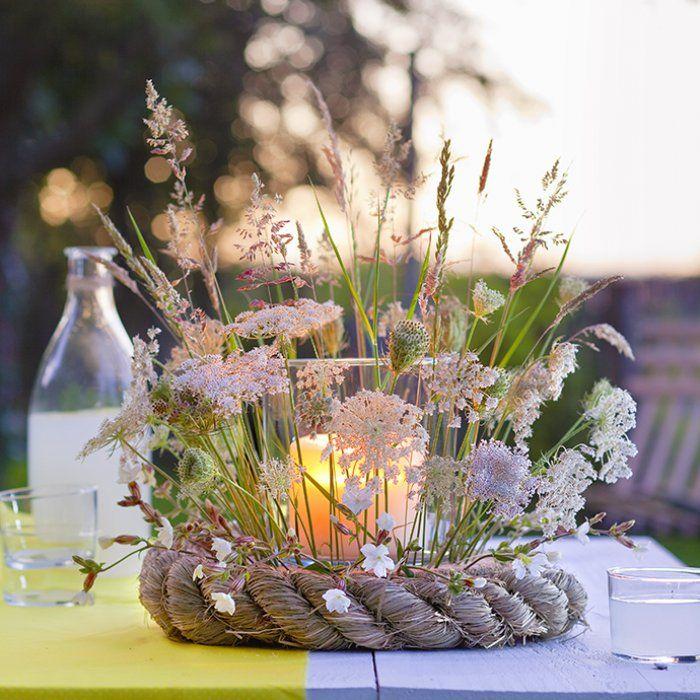 Un photophore entouré de fleurs de graminées