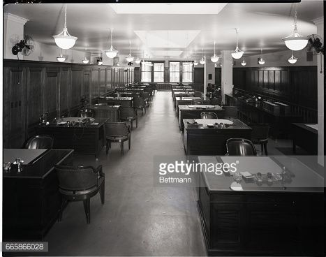 Photograph of the empty interior of a large, business office filled with neatly lined-up desks. Undated photograph.