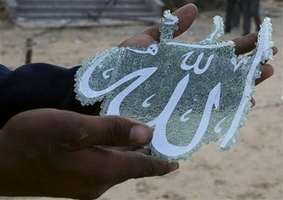 """A piece of broken glass with the word """"Allah"""" written on it. It came from a shattered window of the University of Palestine, which was destroyed during the 2009 Israel operated war on Gaza, a war that killed over 1200 Palestinians."""