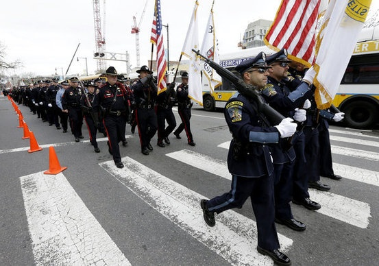Members of a police honor guard lead a column of law enforcement officials into a memorial service for fallen Massachusetts Institute of Technology police officer Sean Collier, in Cambridge, Mass.