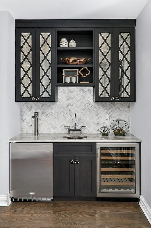 Black mirrored cabinets flank stacked black shelves ...