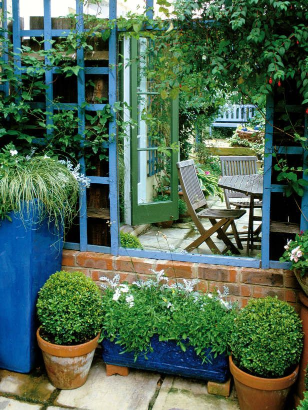 A mirror placed in a garden trellis helps to transform this small space by illuminating it visually and doubling the size of the garden by reflection.