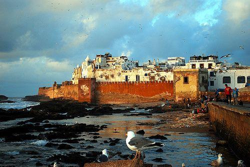 Essaouira, Morocco. The Wall of the Old Medina and the Atlantic Ocean. Essaouira è la città del vento, costante, teso, umido, sempre fresco. E' il vento che riempie la vita di tutti, abitanti e turisti, ogni momento della giornata, che spazza la spiaggia ed il lungomare ed entra nei vicoli. Un vento che ti invita ad indossare un golf od una felpa non appena cala il sole, anche in piena estate.