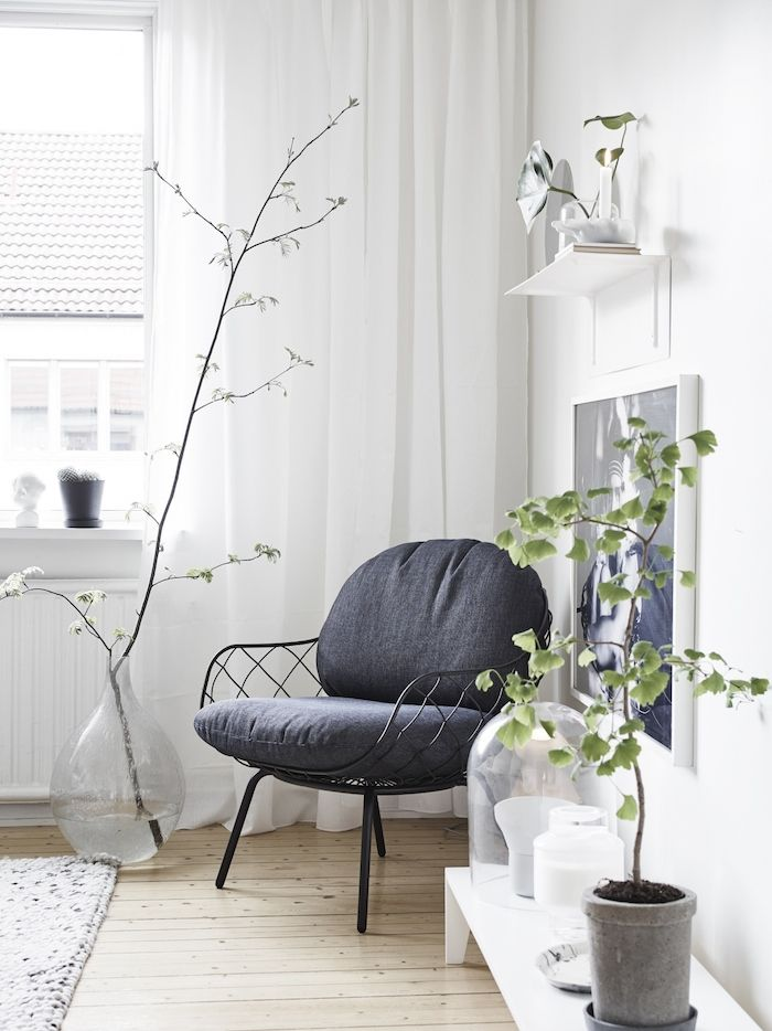 white living room branch in wine balloon green plant white decor grey chair white curtains interior styling..