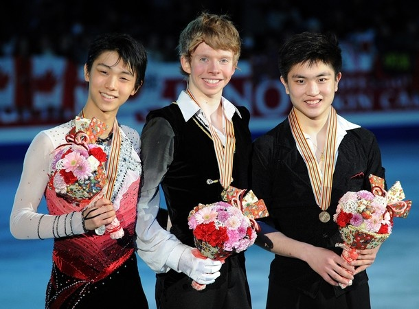 Four Continents figure skating championships mens event winner Canadas Kevin Reynolds (C) poses with second placer, Japans Yuzuru Hanyu (L) and third placed Chinas Yan Han during the awards ceremony in Osaka on February 9, 2013.
