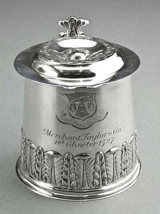 A delightful and attractive silver miniature replica tankard, commemorating the 600th anniversary of the founding of the Merchant Taylors Company in 1327. The tankard is a replica of an original Irish tankard with Dublin hallmarks for 1680. The tankard has acanthus and laurel leaf embossing to the lower body, as well as an embossed cross and floral design on the base. The lid has a scrolled thumbpiece, and the flat stepped lid is decorated with the figure of a mans head (very unusual), with…