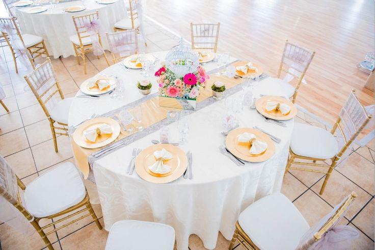 Monte Vista Venue dusty pink and gold table setup with a white tablecloth, gold under plates, gold tiffany chairs and a birdcage with flowers in on a mirror box with two small rose bowl with flowers in as a centerpiece