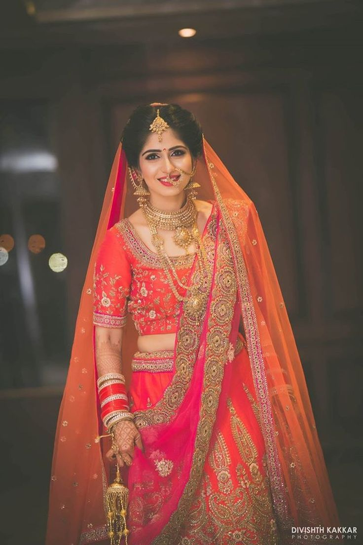 Brilliant combination of orange, pink and gold colored bridal lehenga with eye catching zari work and elegant gold jewelery | weddingz.in | India's Largest Wedding Company | Wedding Venues, Vendors and Inspiration | Indian Wedding Bridal Jewellery Ideas |
