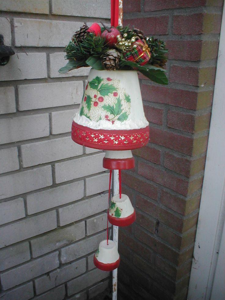 bloempotjes tot kerstklokje gemaakt. 1 grote en 3 kleintjes. Schilderen en met servetten beplakt. rood band op de randen en daarboven 'n randje met latex er op gedaan en glitter er op. Lint er door en bovenop 'n krans die je eigenlijk op 'n kandelaar doet.