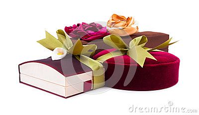 Luxury gift boxes in dark red and brown shades with green satin ribbon and bow isolated over white background.