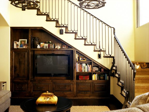 This living room has a customized built-in entertainment unit that makes use of every inch of space available. The stair railing and lighting were custom-made. Fabulous!