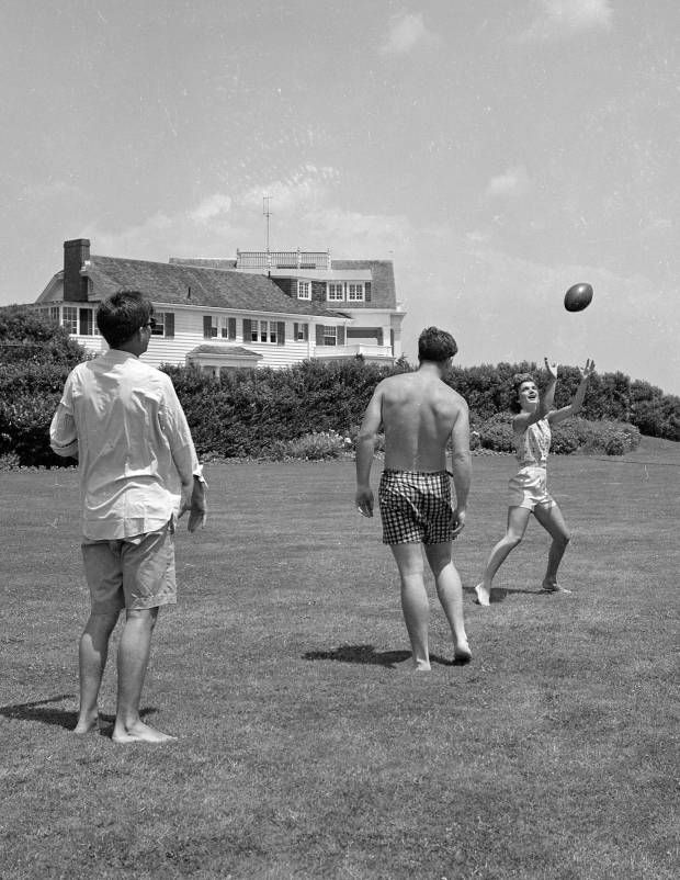 1953  John F. Kennedy, Jacqueline Kennedy, and Edward Kennedy play football on the lawn.