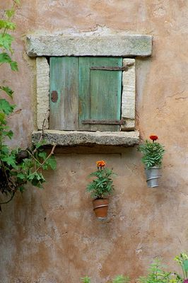 RUSTIC WINDOW IN STONE WALL WITH SIMPLE WALL-MOUNTED CONTAINERS. BRITISH SKY BROADCASTING GARDEN. DESIGNER: FIONA LAWRENSON.