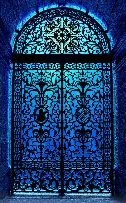 Wrought iron door in blue and turquoise light. Looks like stained glass!