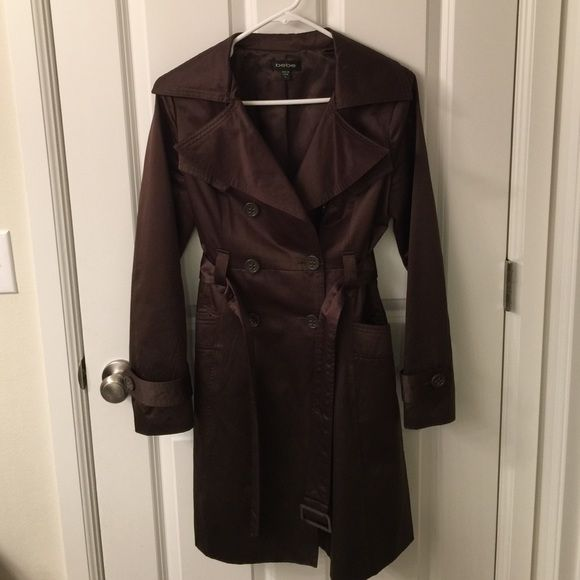 Bebe chocolate brown trench coat size small Pre-loved Bebe chocolate brown trench coat in size small. Could use a cleaning and there is a snag on the interior lining - please see last photo. Besides that good condition! Material has shine to it. 60% cotton and 40% polyester. No trades bebe Jackets & Coats Trench Coats
