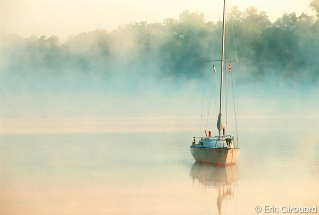 Sailboat in fog on the Richelieu River at sunrise. Seen from Beloeil, looking towards Mont Saint-Hilaire, Quebec, Canada.