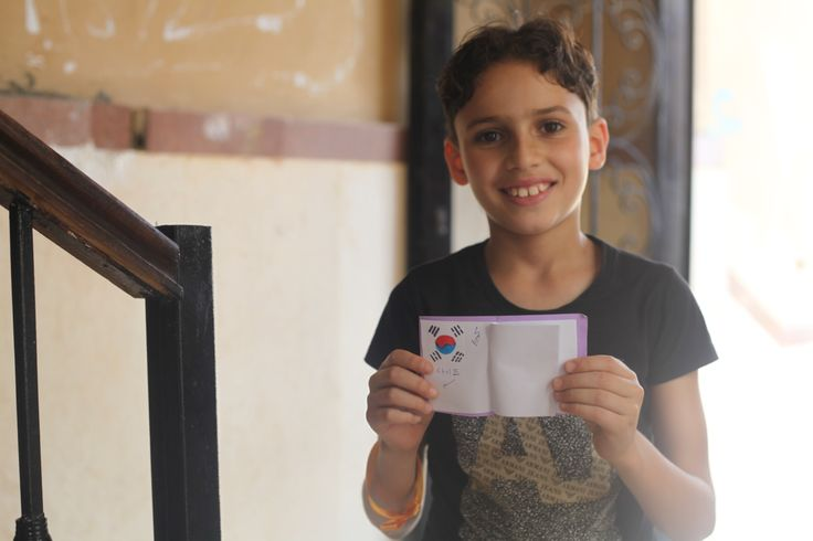 """Activities held in Egypt to mark World Refugee Day: Sayed, a 10 year-old Egyptian boy, shows off his new 'passport', created during the travel-focused """"Safarni"""" session at the coexistence workshop held by Save the Children in our Child Friendly Space (CFS) located in 6th of October City.  Sayed comes to the CFS twice a week with his sister Jana, and both attended the five-day workshop on coexistence that took place in the second week of June."""