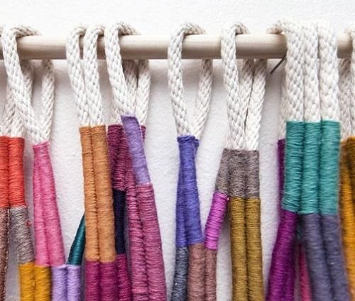 Buy a metal bar and some rope > wrap colorful thread around them. Make a loop at the end for hanging keys and such. Use S hooks if required. These ase Alicia Scardetta wall hangings