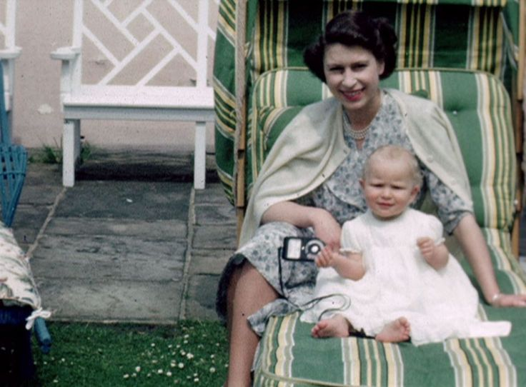 In another clip, Her Majesty The Queen poses for a photograph while a very young Princess Anne appears distracted with the object in her rig...