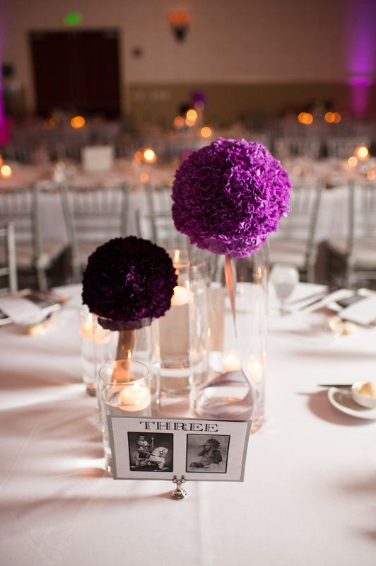 centerpiece arrangement of lavender and purple pomander balls on glass cylinders, surrounded by glass cylinders of floating candles and votives.