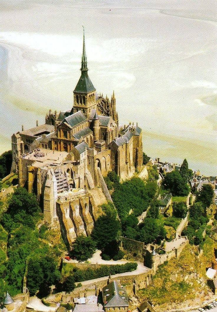 Mont-Saint-Michel and its Bay, France. Perched on a rocky islet in the midst of vast sandbanks exposed to powerful tides between Normandy and Brittany stand the 'Wonder of the West', a Gothic-style Benedictine abbey dedicated to the archangel St Michael, and the village that grew up in the shadow of its great walls.
