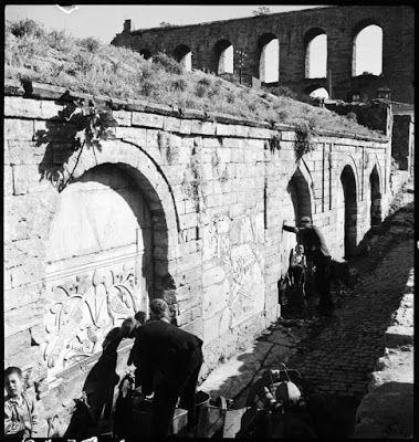 πηγή Kırkçeşme και το Υδραγωγείο του Ουάλεντος (Bozdoğan Kemeri), Απρίλιος 1935. Άνδρες και παιδιά παίρνουν νερό από την οθωμανική κρήνη που είναι διακοσμημένη με βυζαντινά ανάγλυφα. Το Υδραγωγείο διακρίνεται στο βάθος να δεσπόζει πάνω από την πόλη αναμειγνύοντας ακόμα περισσότερο το αρχαίο με το σύγχρονο. ©Nicholas V. Artamonoff Collection, Image Collections and Fieldwork Archives, Dumbarton Oaks.