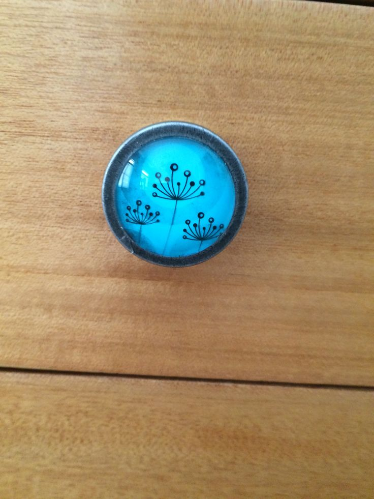 Knobs match wallpaper, made from brass and glass.