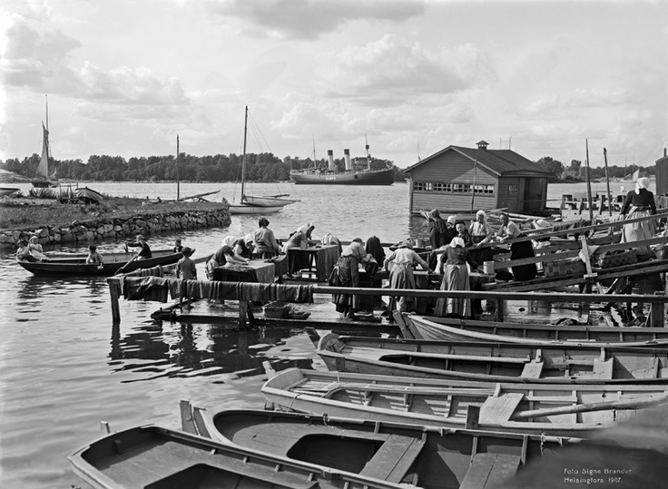 Kuvassa mattolaituri Munkkisaaren salmessa. Taustalla Jätkäsaari ja jäänmurtaja s/s Sampo. Foto: Signe Brander, 1907.