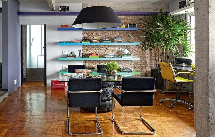 Na sala, a área do escritório tem prateleiras laqueadas coloridas de roxo, tons de azul, verde e coral. A mesa de jantar é improvisada com tampo de vidro e três pneus. O ambiente foi projetado pelo arquiteto Diogo Oliva