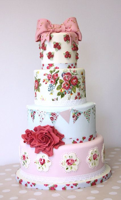 Cath Kidston inspired vintage wedding cake. Two tiers are handpainted, as well as the bow. The bunting patterns were printed onto edible sheets.