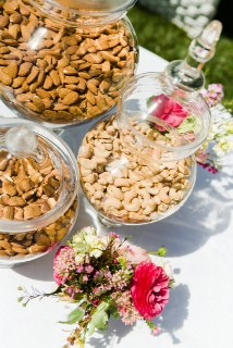 Glass canisters filled with nuts like almonds and cashews not only give your wedding guests a healthy snack, but they add great color to your wedding buffet table.