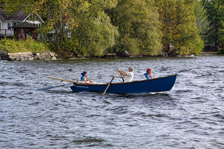 Rowing on Magog River - Father and daughters crossing Magog river in a rowing boat - Magog, Quebec, Canada